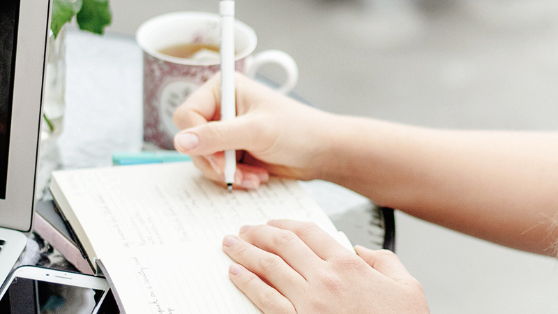 a girl outside drinking coffee while writing down tasks in her planner