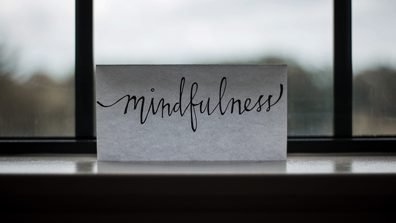 a note with the word mindfulness written on it in front of a window